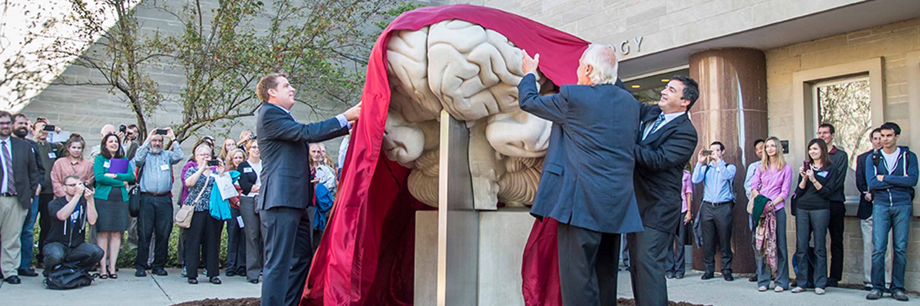 three men in suits unveil human brain statue in front of crowd