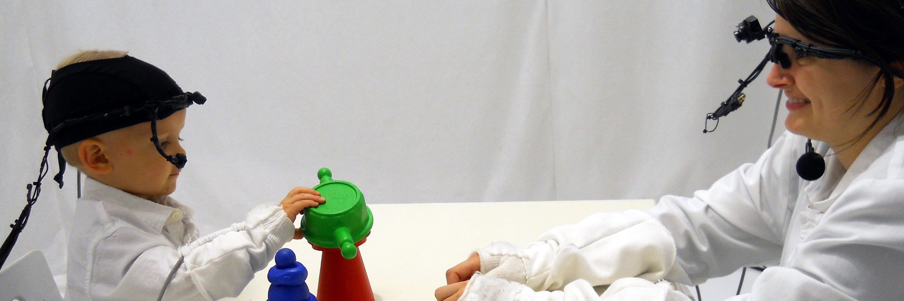 baby and woman playing with toys during an experiment