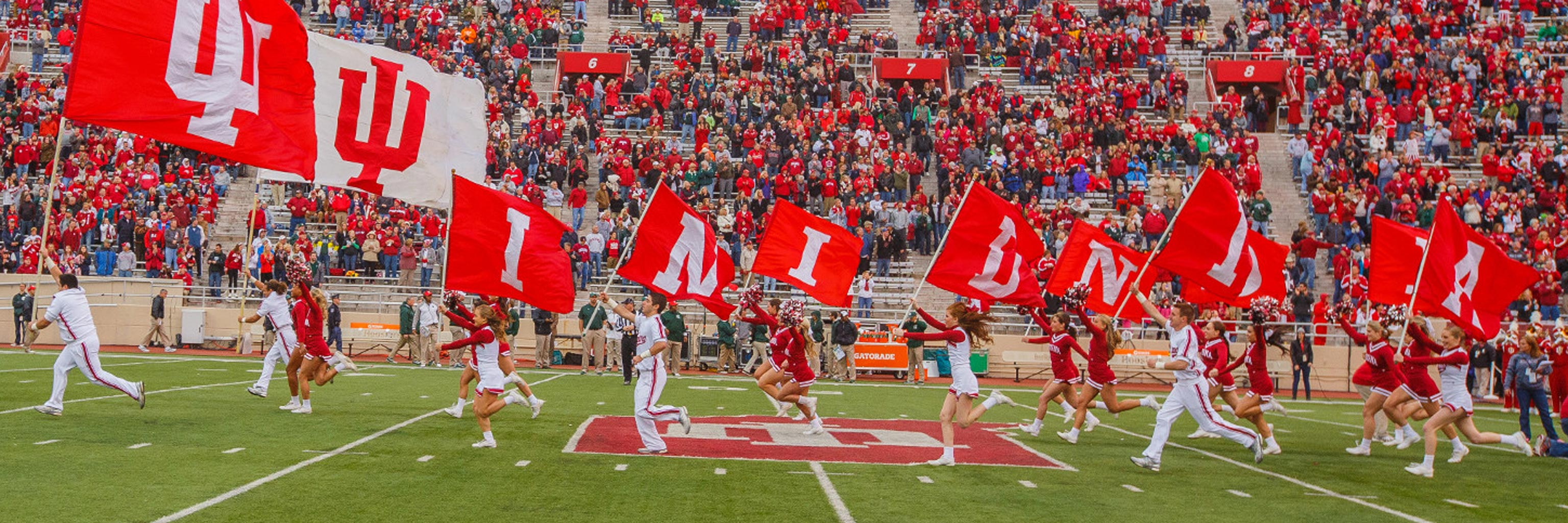 Indiana University pep squad running down football field during a game
