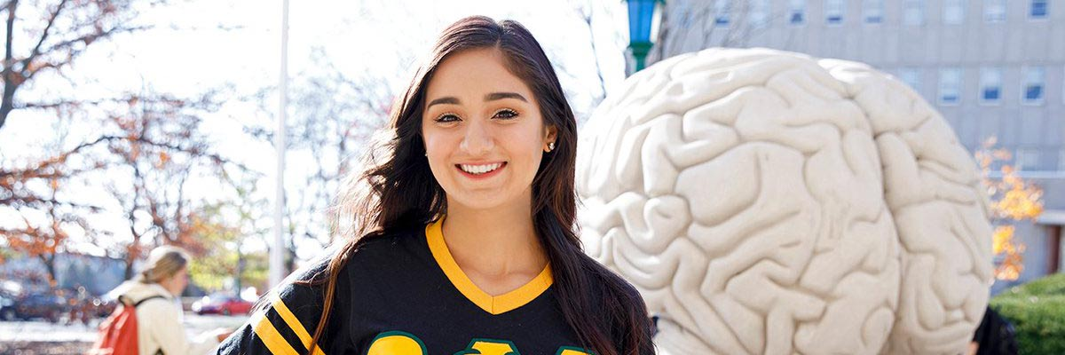 Smiling student standing in front of the human brain statue