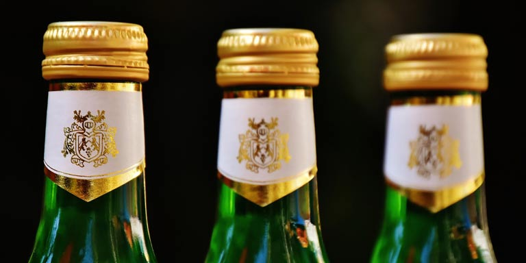 three green bottles of beer with gold caps