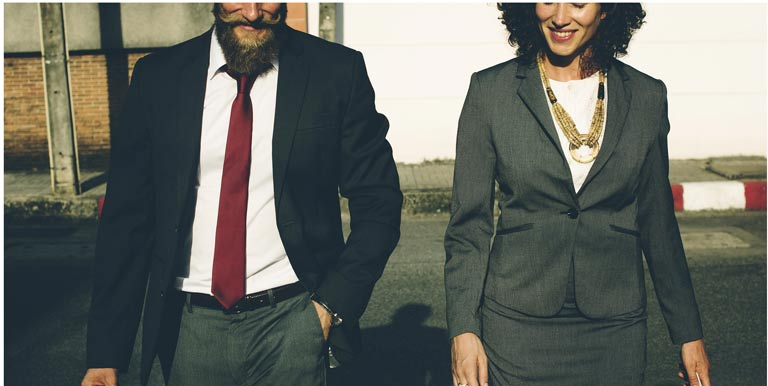 man and woman in business suits walking
