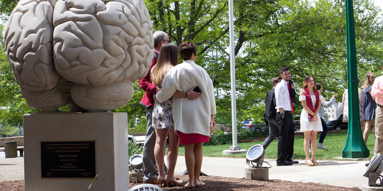 family taking pictures with graduated student in front of human brain statue