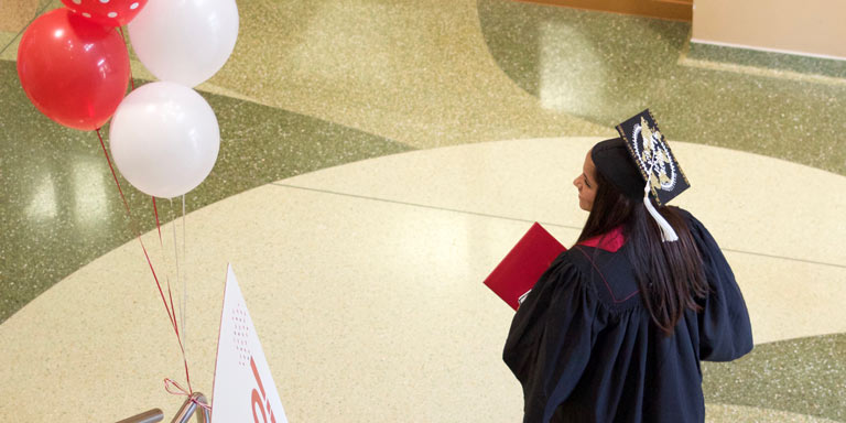 student in cap and gown walking inside a building atrium