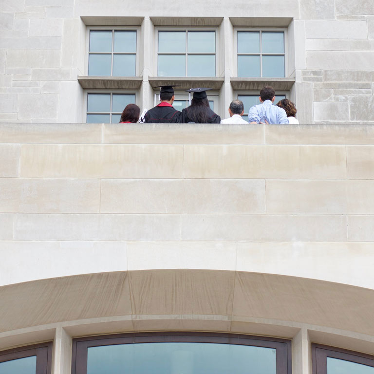 graduated student taking pictures with family on a balcony